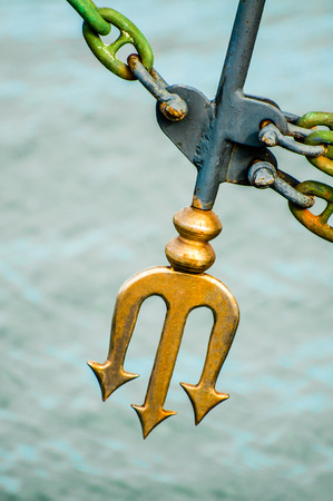 worshipped: A fork of the Roman god Neptune on the bow of a yacht symbolises protection from the ocean and the elements. Stock Photo