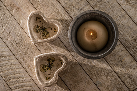 stoneware: Two heart decorations on a white whashed wooden table next to a lit candle in a  stoneware pot all in low directional light of the late afternoon.