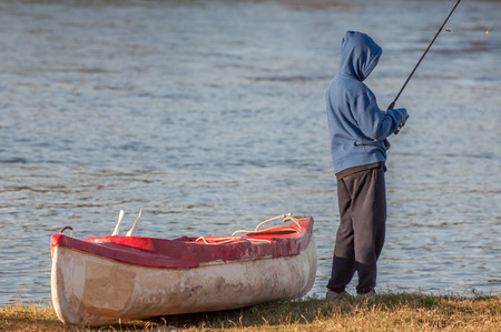 black white kayak: Boy, standing next to canoe on the banks of a river, with fishing rod in hand, busy fishing.