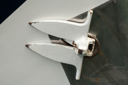 vessel sink: Up close view of an anchor of a yacht, retracted against the hull of the vessel. Stock Photo