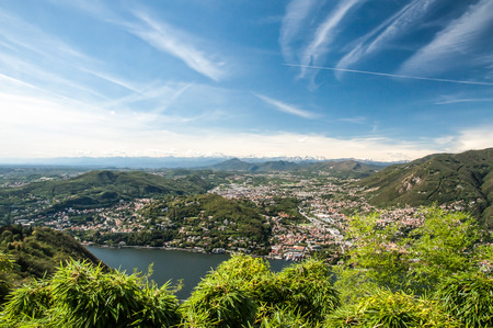 arial views: A view of Lake Como, the Town called Como and the Alps in the far distance with blue skys and white clouds.