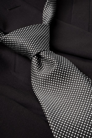 loosely: A black and white dotted tie, already with a knot, lying loosely on a dark suit.