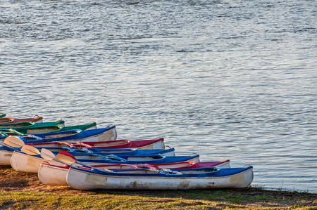 lined up: Several kayaks lined up, one next to the other, on the river bank and ready for the adventures ahead. Stock Photo