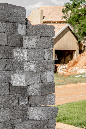 building material: Building material stacked next to the imcomplete house that it is intended for.
