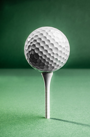 positioned: A white golf ball positioned on top of a tee, ready for the tee shot.