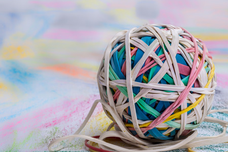A ball of elastic bands of many different colours placed on a piece of paper that has also been coloured in many different vibrant colours.