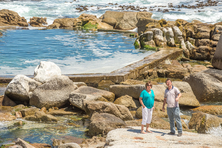 man made: Man and elderly woman standing by a man made tidal pool while looking in the other direction.