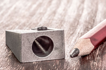parer: Close up view of a prism pensil sharpener and a pencil that needs some sharpening next to it.