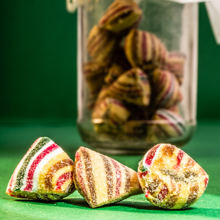 viewer: Three pieces of candy up close near the viewer on a green background with the bottle where they came from far in the back. Stock Photo