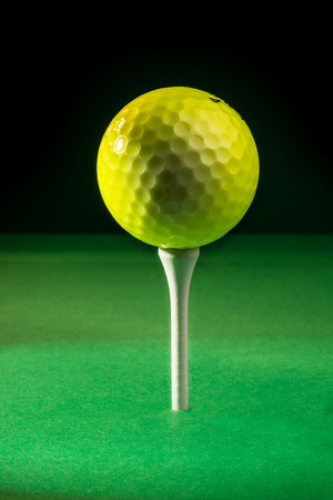 positioned: A yellow golf ball positioned on top of a tee, ready for the tee shot.