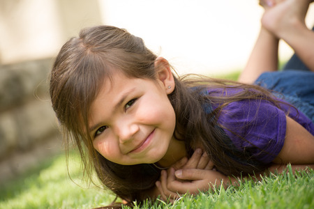 Little girl lying on the lawn on her belly with feet in the air and a smile on her face.