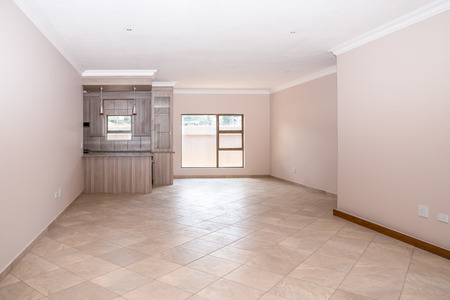 A vacant livingroom of a newly build house, with tiled floors, newly painted walls, and part of the kitchen in the background.