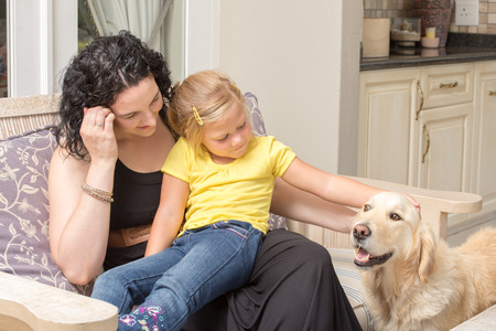 Mother and daughter sitting together on a chair on the porch of their home while stoking the golden retriever pet dog.