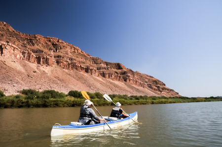 Two people in a double kayak paddling the Orange River.