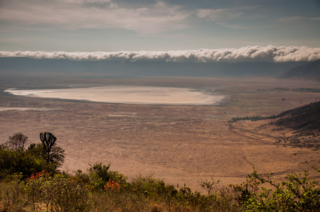 other side of: Clouds on the rim of the ngorongoro crater as viewed from the other side of the rim, with the lake clearly visible.