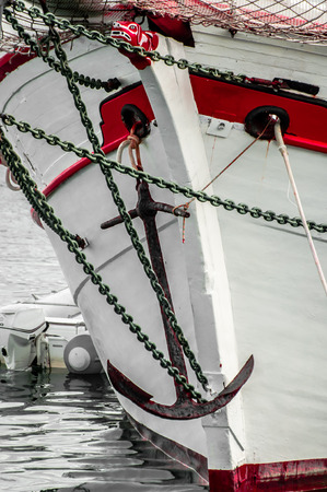 ship bow: The bow of an old sailing ship with old anchor and neatly painted in red and white.