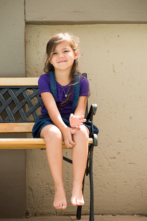 arms behind head: A little girl sits on a bench outside in the back garden of her home. Stock Photo