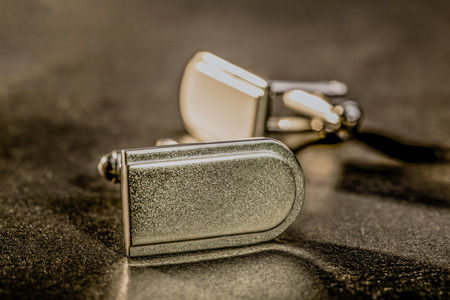 french cuffs: A set of cufflinks lie on a table. Stock Photo