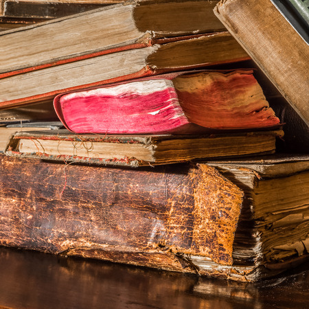 Old books lie stacked in a messy order on a book shelf photo