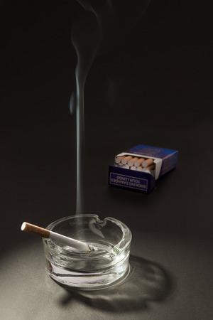 un healthy: A lid cigarette lies burning in an ashtray, with the smoke floating up in to the air, with an open packet of cigarettes in the background.