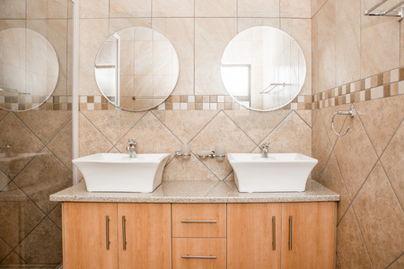 mirror: The interior of the bathroom of a brand new house, showing the double basins, mirrors and shower screen. Stock Photo
