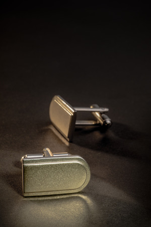 french cuffs: A pair of cufflinks on a dark counter top.