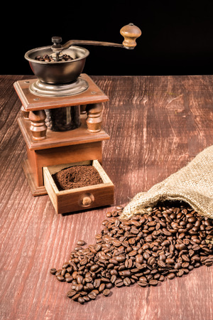 hessian bag: Coffee beans ly spilled from a hessian bag on a wooden table with an old grinder in the back.