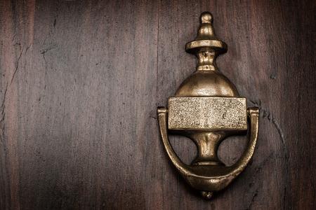 door knocker: A copper door knocker on a wooden front door.
