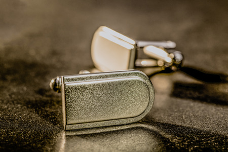 cuff: A pair of cuff links lie together in low warm light on a dark surface.
