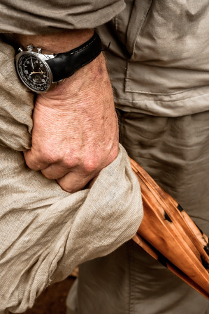 rolled up sleeves: A view of the right hand side hand of an elderly gentleman holding on to a closed umbrella and a khaki coloured piece of cloth. H