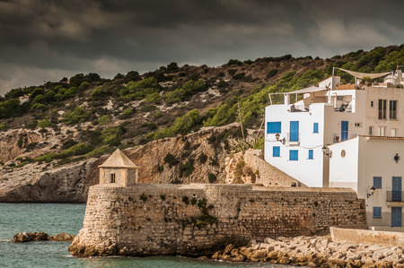 days gone by: A white painted residential building with blue doors and window shutters, stand on the edge of the see just behind a thick fortress wall, overlooking the sea in Ibiza. Stock Photo