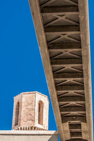 shortest: The bottom of a concrete pedestrian bridge viewed from below with an old stone watch tower  to the left, all set against a blue sky.