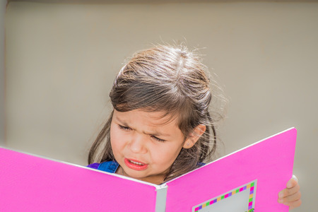 girl sitting: A little girl sits outside, reading a big book with a pink cover. Stock Photo