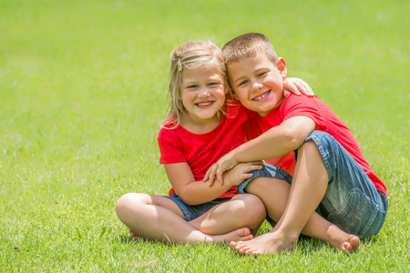 looking at viewer: Two children whom are brother and sister are sitting on the green lawn with red t shirts and blue jean shorts with big smiles looking at the viewer at giving each other a big hug, on a beautiful summer day. Stock Photo