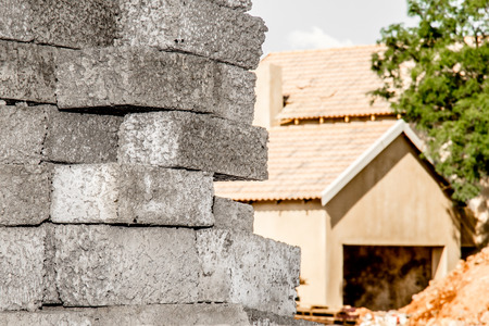 suburbia: A close up view of stacked grey concrete bricks infront of an unfinished house.