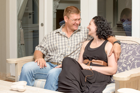 sit around: A young couple sit togehter on a bench out on the patio, man has arm around women,s neck, they look at each other while smiling and laughing happily.