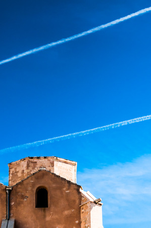 warehouse building: Two diagonal aeroplane trails cross the blue sky high above an old warehouse building in Marseille, France.