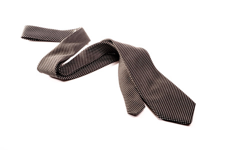 superficial: A black tie with white dots is situated semi folded in a zick zack way on a white isolated background
