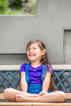 legs folded: A pretty little girl,with long dark hair, and purple shirt, sits on an outside bench in the garden with her legs folded, while laughing with joy.