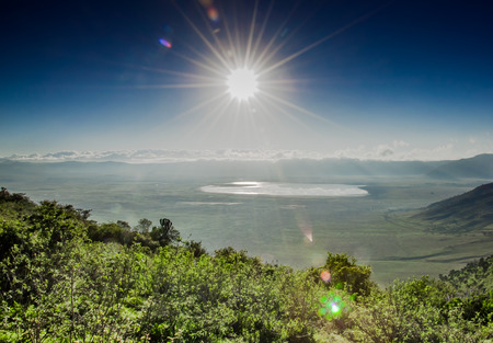 clowds: A view of the Ngorongoro Crater, with lake Magadi visbible in the distance infront of the clowds which cover the crater rim on the far side, as it is viewed in to the sun from the top of the crater rim. Stock Photo