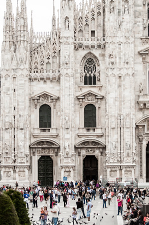 buttresses: A crowd of people move around in front of the Cathedral of Milan of whom most are tourists coming to view the 5th largest church in the world.