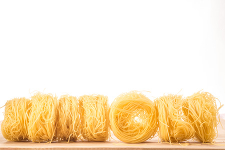 Seven balls of Angel's Hair spaghetti lie in a straight line on a wooden surface, in front of a white background.