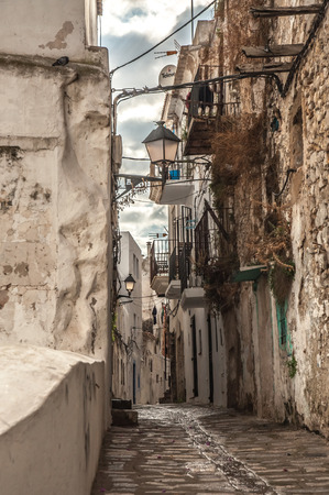 cramped: An old and narrow road laid with stone and pebbles lead in to the old town of Ibiza flanked by old houses on both sides. Stock Photo