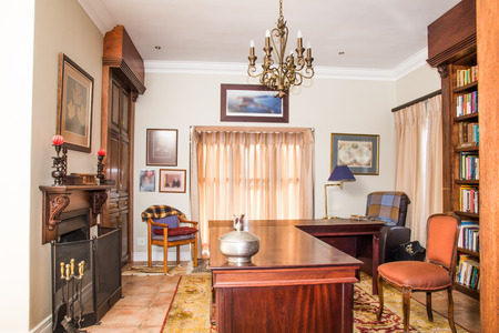 clean home: A private study in a residential home complete with table and furniture as well as a fire place.