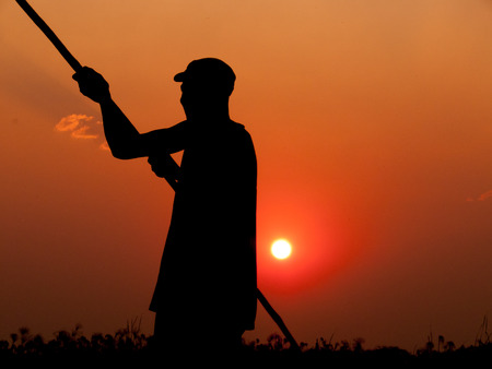 dugout: A skilled poler pushes his dugout boat forward in the Okavango Delta while standing upright in the boat and seen as a silhouette arms stretched out while holding the pole in both hands behind him the yellow glow of the sun setting in a beautiful red orang