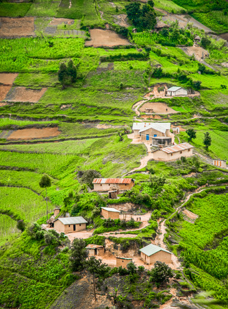 an agricultural district: A view from high up of some houses and green agricultural land set against slope in the rural area of the Kabale district in Southern Uganda.