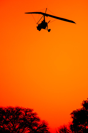 An ultralite aircraft comes in for a landing as the sun is setting revealing only a black sihoutte of the aircraft and the tips of the trees against a red orange sky.