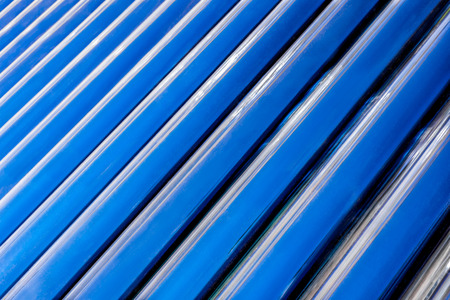 convection: A diagonal and up close view of the convection tubes of a solar geyser as they fill the horizontal frame to create an abstract background image of blue and black diagonal lines.