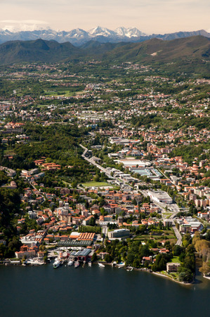 arial views: A vertical view of Lake Como in the  front, the town called Como behind, and the Alps on the horizon.