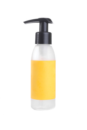 containment: A plastic bottle with a yellow label and a black top with snoute stand on a white isolated background.